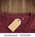 price tag hang over brown t-shirt on wood background - stock photo