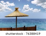 Straw beach umbrella with beautiful cloudscape background - stock photo