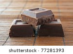 Three blocks of dark chocolate over wooden mat - stock photo