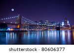 New York City's Brooklyn Bridge and Manhattan skyline illuminated at night with a full moon overhead. - stock photo