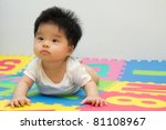Portrait of a little Asian baby girl crawling on floor - stock photo