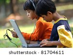 Young children, boy and girl using laptop and listening to digital music in outdoor scene - stock photo