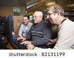 Volunteers teaching a senior how to use a computer - stock photo