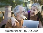 Mature couple laughing while sharing a digital tablet - stock photo