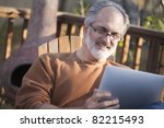 Senior man using a digital tablet outdoors - stock photo