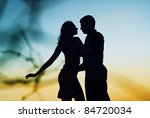 Beautiful couple in love at sunset. Silhouette guys and girls at sunset. They dance. - stock photo