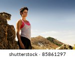 Young woman in running outfit standing on a dry mountain path. - stock photo