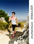 Young smiling woman running on a dry mountain path. - stock photo