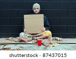 Young homeless man holds blank cardboard for your own text - stock photo