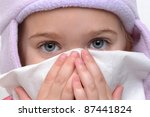 little girl blowing nose with tissue - stock photo