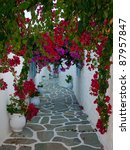 Flowers on the narrow streets of the Mediterranean. Mykonos. Greece. - stock photo