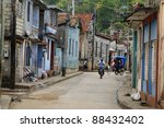 Classic cuban backstreet with bike and rickshaw - stock photo