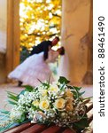 The beautiful wedding bouquet flowers lays on a bench, on a background a newly-married couple. Focus on a bouquet. - stock photo
