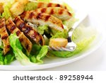 Caesar Salad with grilled chicken on white plate. - stock photo