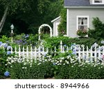 beautiful garden setting with flowers and white picket fence - stock photo