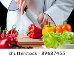 Food preparation – chef cutting bell peppers - stock photo