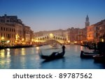 Rialto Bridge and gondolas at a foggy autumn evening in Venice. - stock photo