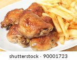 A serving dish piled with roast lemon chicken thighs and French fries, or chips - stock photo