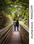 man and woman taking a walk in the woods, on a wooden bridge - stock photo