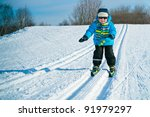 Cute little boy skiing downhill - stock photo