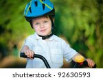 Close up portrait of a cute little boy in a bicycle - stock photo