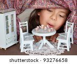 Little girl looking through a window into a doll's house like in alice in wonderland - stock photo