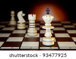 Chessmen on a chess board. An art dark background. - stock photo