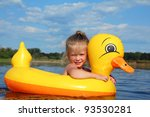 little girl bathes in summer river in inflatable duck - stock photo
