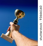 Close up of trophy, hand and blue sky - stock photo