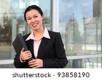A pretty Chinese business woman smiling outside office building - stock photo