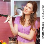 Attractive young woman with big spoon smiling and joyful in the modern kitchen - stock photo