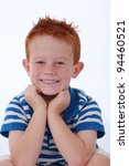Red head boy wearing blue striped shirt with happy and smiling expression on face - stock photo