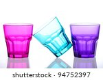 Three colored glasses placed on a white backround one not standing straight - stock photo