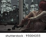 Alone beautiful woman sitting on window and looking on night city - stock photo