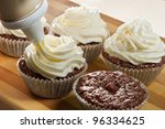 Decorating chocolate muffin with vanilla cream - stock photo
