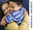 A mid adult African American woman affectionately hugs her young son. Square shot. - stock photo
