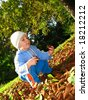 Autumn play, little boy play with chestnut and leaves - stock photo