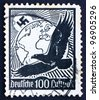 GERMANY - CIRCA 1934: a stamp printed in the Germany shows Swastika Sun, Globe and Eagle, circa 1934 - stock photo