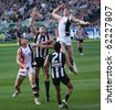 MELBOURNE - OCTOBER 2: St Kilda's Brendon Goddard leaps high over Collingwoods Darren Jolly  during  Collingwood's AFL Grand Final win at the MCG - October 2, 2010 in Melbourne, Australia - stock photo