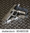 pistol on steel with some water droplets and reflections - stock photo